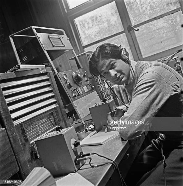 Employee listens in and monitors radio broadcasts from various parts of the British Empire at a BBC Monitoring Service establishment in England...