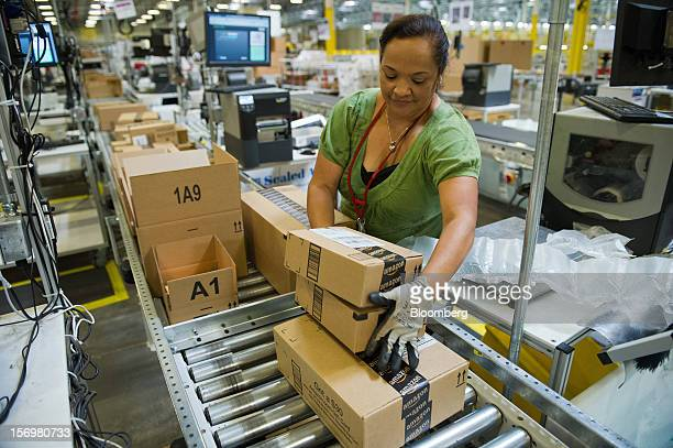 Employee Maria Miller loads boxes onto a conveyer belt for shipping at the Amazoncom Inc distribution center in Phoenix Arizona US on Monday Nov 26...
