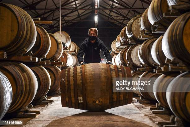 Employee Matthew Coulson poses for a photograph with whisky casks in the bonded warehouse at The Glenturret Distillery in Crieff, central Scotland,...