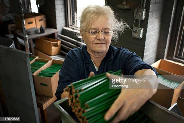 Employee May Ann Davis loads a hopper with pencils at the General Pencil Co's factory in Jersey City New Jersey US on Wednesday June 22 2011 General...