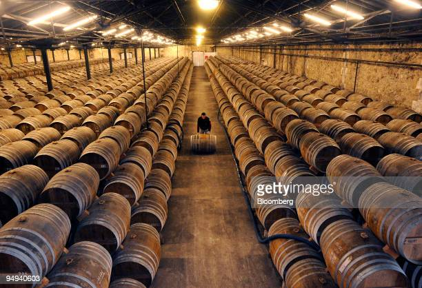 Employee Michael Meunier moves a barrel at the Remy Martin distillery in Cognac France on Tuesday April 14 2009 Remy Cointreau SA France's second...