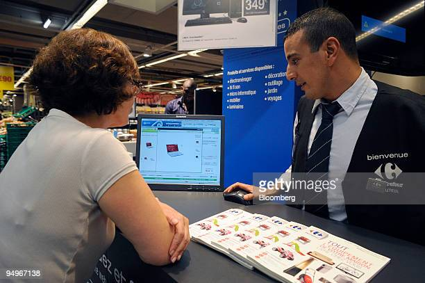 Employee Mohamed Naaimi right assists a customer in a Carrefour supermarket in Paris France on Thursday Aug 20 2009 Carrefour announce earnings next...