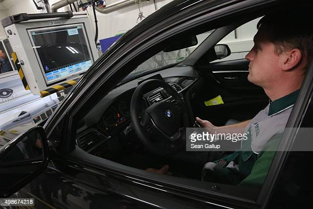 DEKRA employee monitors a car undergoing standard emissions testing under laboratory conditions during a workshop for media on automobile emissions...