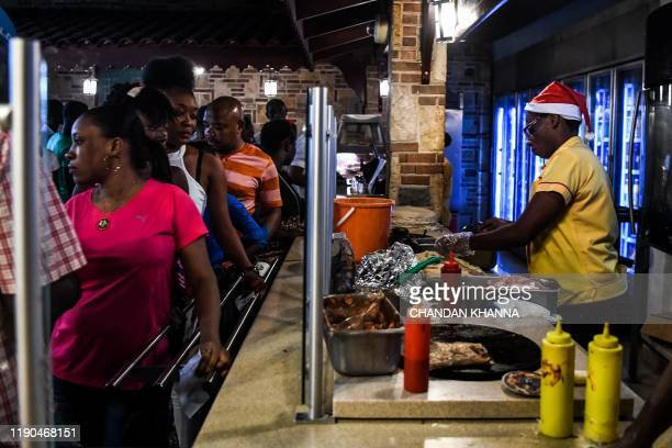 Employee of a fast food joint and confectionery works inside the shop wearing a Santa Claus hat during Christmas eve in PortauPrince on December 24...