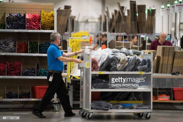 A employee of American electronic commerce company Amazon pushes a trolley with shipping items in Bad Hersfeld central Germany on December 7 2017 To...
