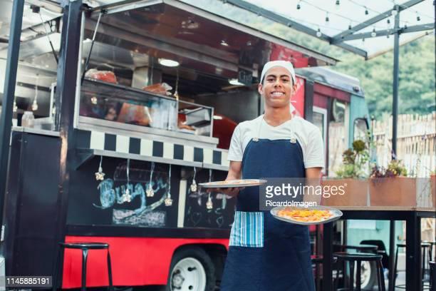 medewerker van food truck toont klaar pizza's - food truck stockfoto's en -beelden