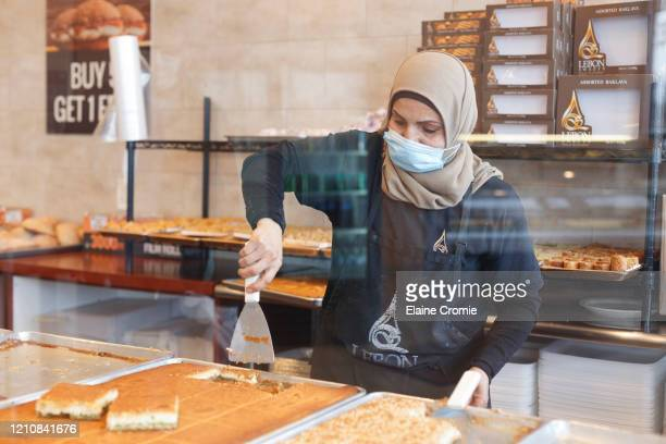 Employee of Lebon Sweets, Dona Awada, prepares sweets in between serving customers on the first day of Ramadan on April 23, 2020 in Dearborn Heights,...