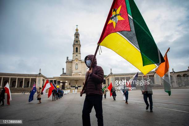 Employee of the sanctuary parades at the end of the mass with the flag of Mozambique during the apparition of Our Lady of Fatima. Due to the COVID-19...