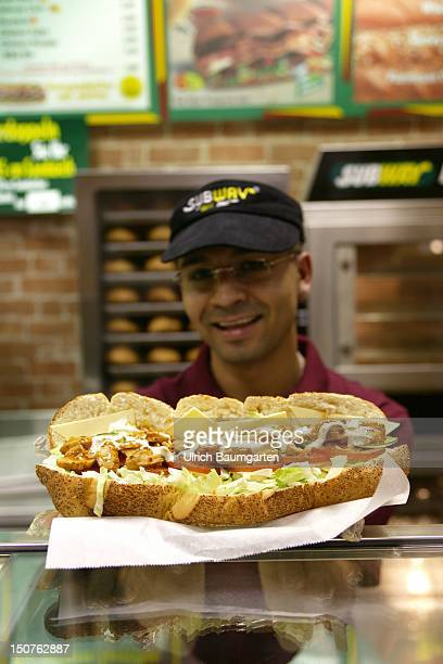Employee of the US American sandwich fastfood chain Subway with a sandwich