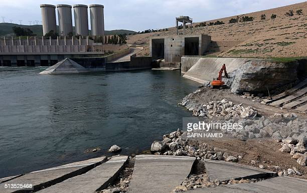 A employee operates an excavator as he works at strengthening the Mosul Dam on the Tigris River around 50 kilometres north of the Iraqi city of Mosul...
