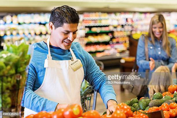 Employee or produce manager stocking vegetables in grocery store