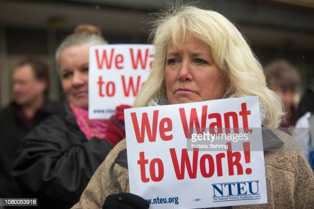 IRS employee Pam Crosbie and others hold signs protesting the government shutdown at the James V Hansen Federal Building on January 10 2019 in Ogden...