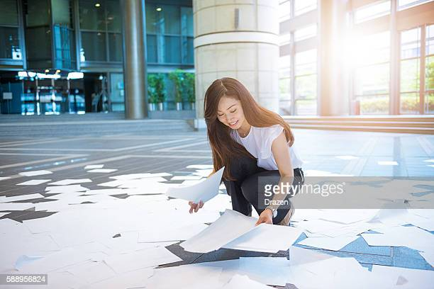 Employee picking up papers from the ground in corporate headquarters
