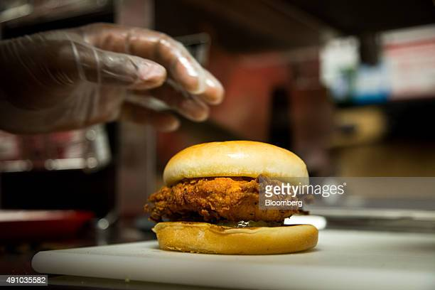 A employee picks up a fried chicken sandwich during an event ahead of the grand opening for a ChickfilA restaurant in New York US on Friday Oct 2...