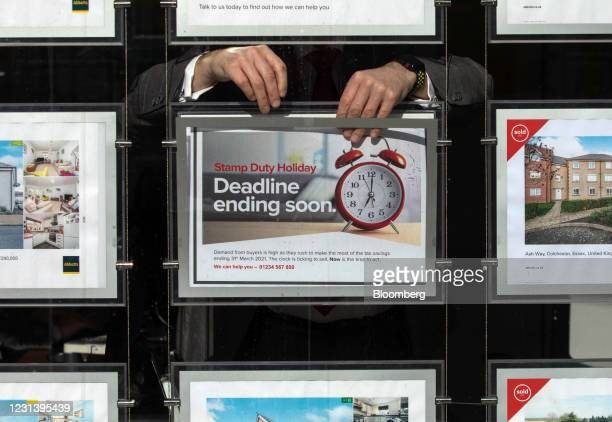Employee places a sign advertising the end of the stamp duty holiday in to the window of an estate agents in Colchester, U.K., on Friday, Feb. 26,...