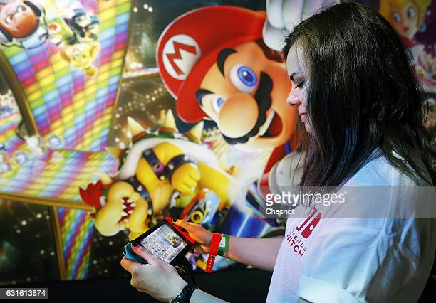 A employee plays the 'Mario Kart 8 Deluxe' video game on a Nintendo Switch games console during the new console's unveiling by Nintendo Co on January...