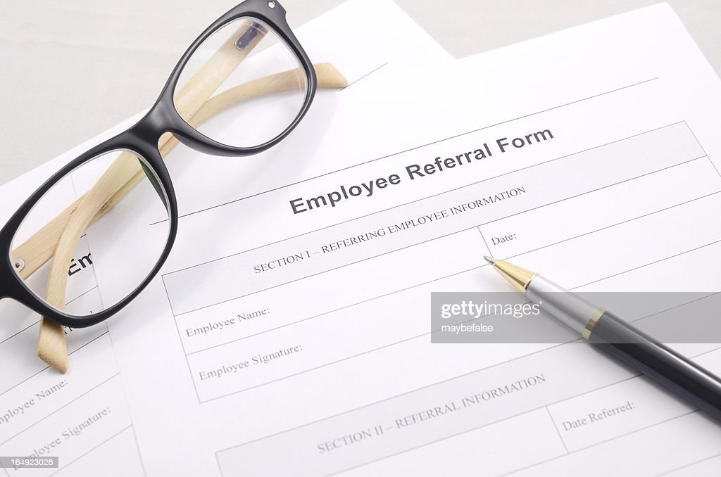 Employee Referral Form With A Pen And Glasses On A Desk Stock Photo