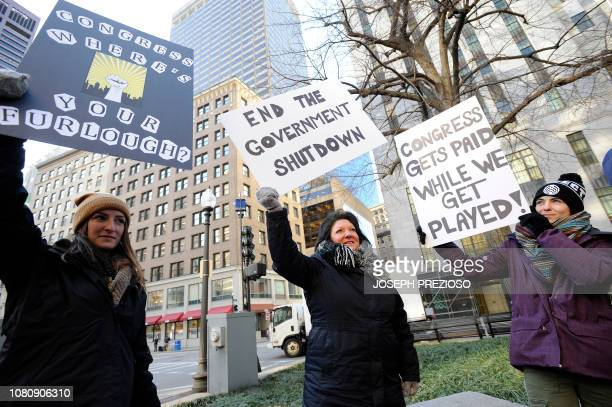 EPA employee Rosanne SawayaObrien holds her sign calling for an end to the government shutdown during a rally and protest by government workers and...