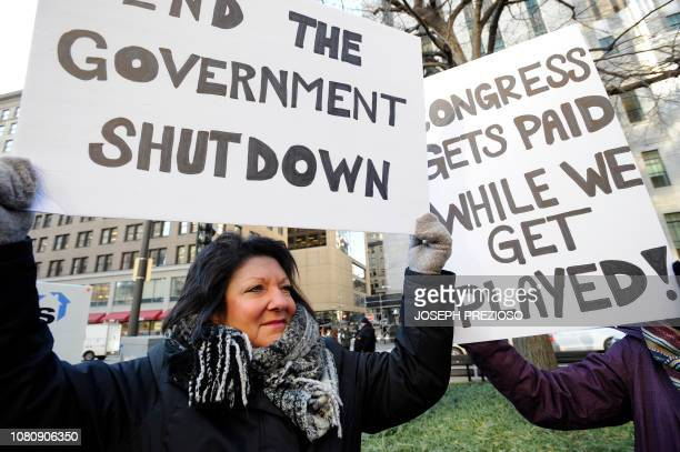 EPA employee Rosanne SawayaObrien holds her sign during a rally and protest by government workers and concerned citizens against the government...