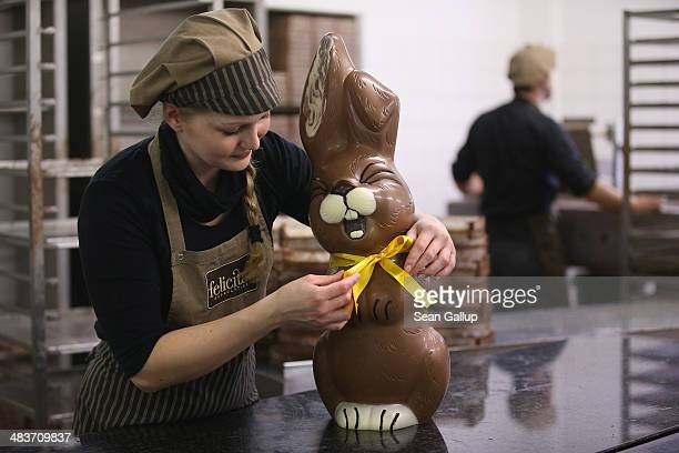 Employee Sandra Jaeckel at the photographer's request adjusts a ribbon around the neck of a giant chocolate Easter bunny at the production facility...