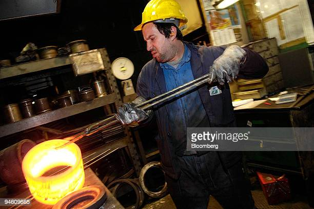 Employee Santino Leonetti lifts a molten ballbearing casing at the Massucco Industrie ballbearing factory in Castellamonte near Turin Italy on Friday...