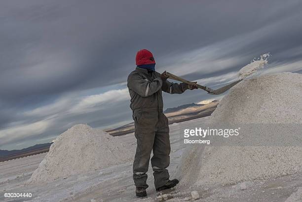 A employee shovels salt into a mountain at the Salar de Uyuni in Potosi Bolivia on Sunday Dec 11 2016 Bolivia has the largest lithium deposits of any...