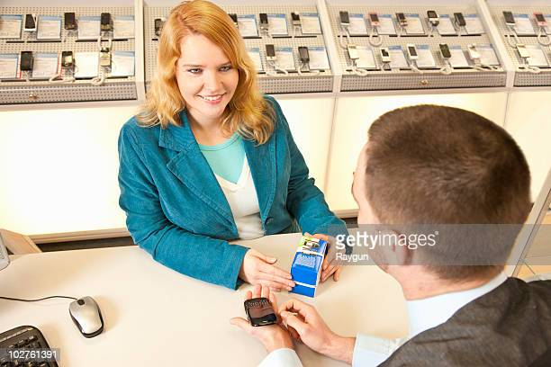 Employee showing a mobile to a customer