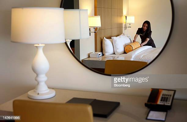 Employee Sofia Padilla demonstrates how to prepare a room for guests in this arranged photograph at the JW Marriott LA Live hotel in Los Angeles...