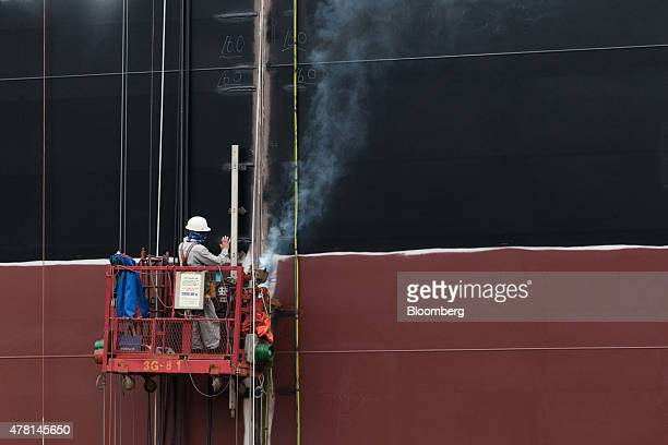 A employee stands on an elevated platform while working on a ship under construction in the dry dock at the Hyundai Heavy Industries Co shipyard in...