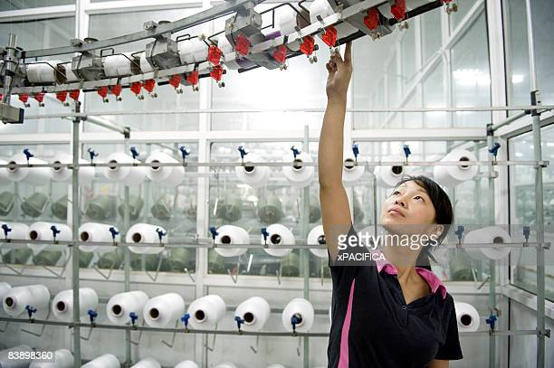 a employee tending to a knitting machine. - textile industry stock pictures, royalty-free photos & images