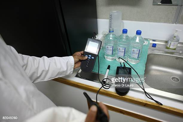 employee tests the level of chlorination in a sample of water at the water testing laboratory at the Camp Bastion Water Bottling Plant on July 21...