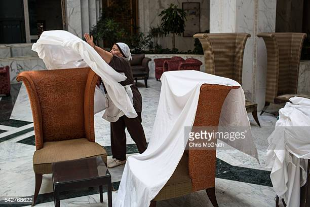 A employee throws sheets over lobby furniture at the closed Imperial Marhaba Hotel on June 24 2016 in Sousse Tunisia The Imperial Marhaba hotel was...
