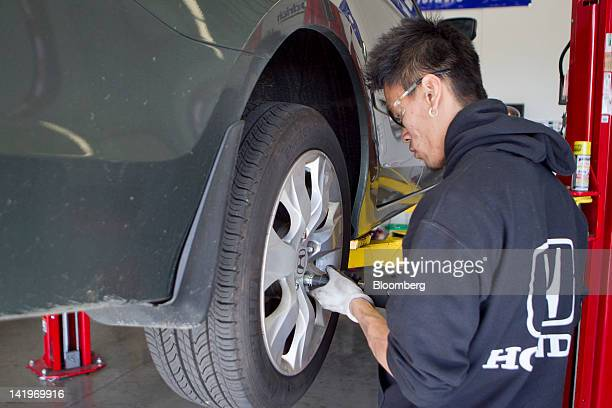 Employee Tommy Le rotates the tires of a Honda Motor Co Accord vehicle inside the garage of a BJ's Wholesale Club Inc store in Falls Church Virginia...