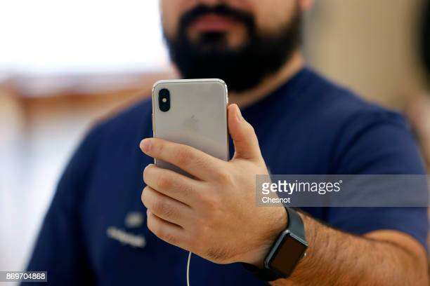 A employee uses the new facerecognition software on the Apple iPhone X the new model of Apple smartphone at the Apple Store SaintGermain on November...