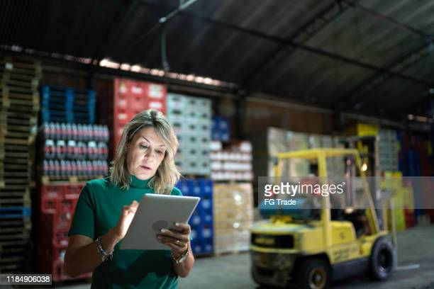 employee using digital tablet at warehouse - market retail space stock pictures, royalty-free photos & images