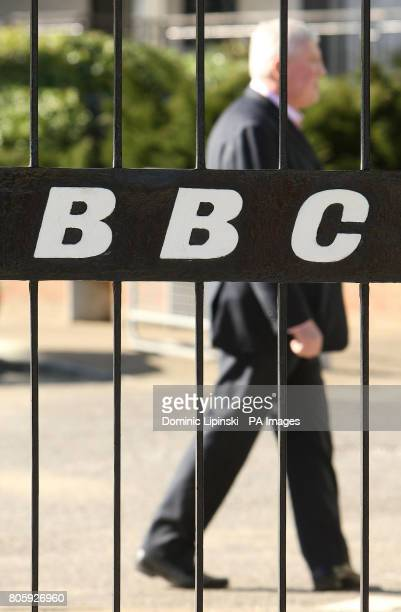 A BBC employee walks past a BBC logo on a gate at BBC Television Centre after it was confirmed the closure of digital radio stations 6 Music and the...
