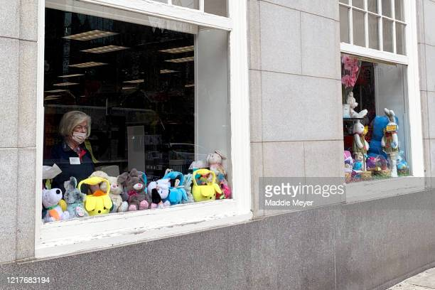 CVS employee wearing a face mask looks onto Boylston street over an Easter display on April 08 2020 in Boston Massachusetts A stayathome order by by...