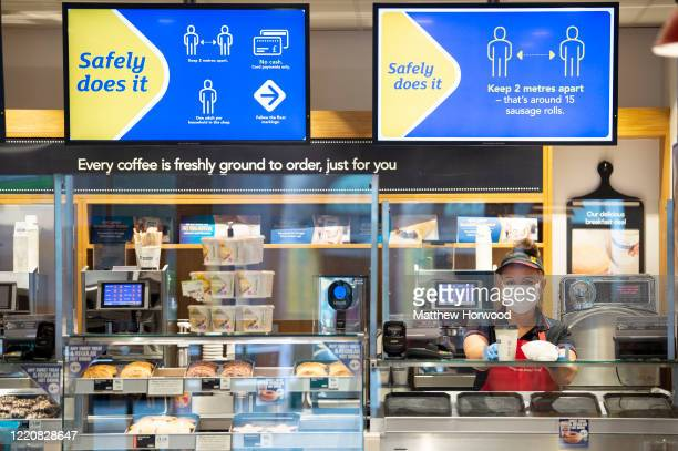 Employee wearing a surgical face mask at a Greggs store serves a customer as the chain begins to re-open its stores as lockdown restrictions are...