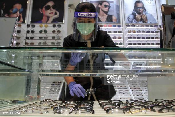 A Employee wears a face shield as she arranges a eyeglasses at a optic shop in Malioboro Mall Yogyakarta after the shops were allowed to reopen amid...