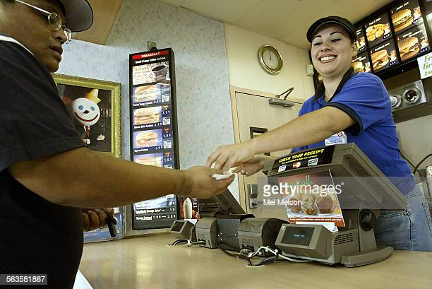 Employee Wendy Martinez gives a customer back his change after taking his order at a Jack in the Box on Glendale Blvd in Los Angeles on Friday...