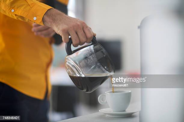 employee with sling pouring coffee into cup at work - fülle stock-fotos und bilder