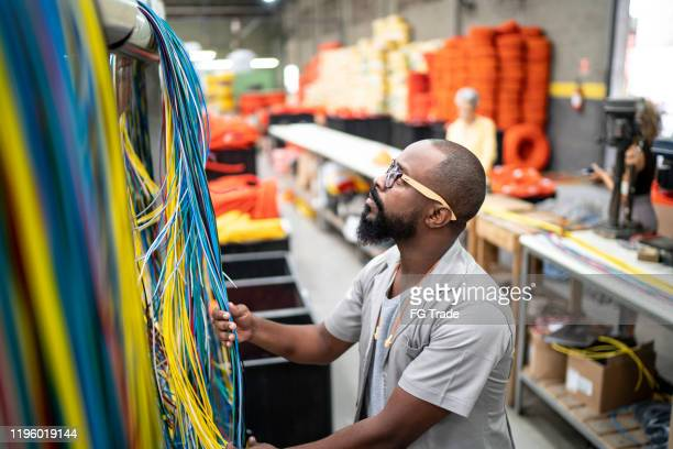 employee working with wires in industry - cabo imagens e fotografias de stock