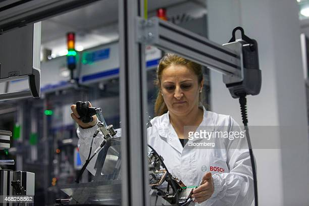 A employee works on the Bosch multi purpose camera automobile driver assistance sensor assembly line at the Robert Bosch GmbH plant in Blaichach...