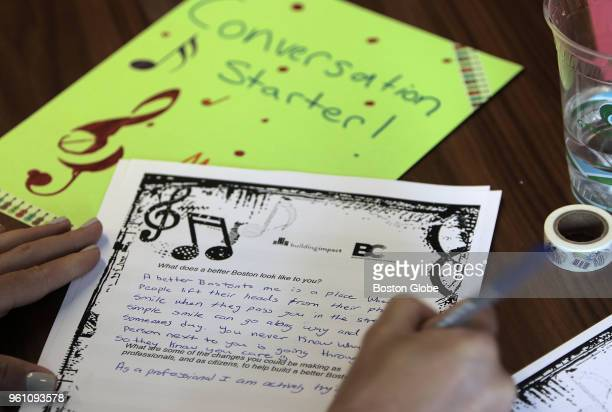 JLL employee writes a response as part of a letter exchange program with the Boston Children's Chorus in Boston on May 3 2018 For a race and social...