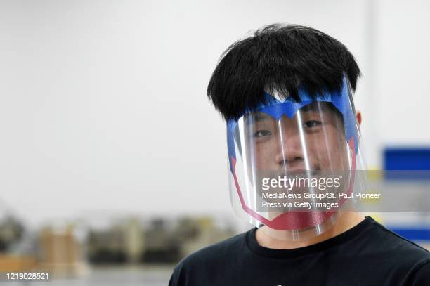 Employee Zhi Gao models a superhero face shield at the Vomela Companies, a St. Paul manufacturer of signs for retail and sports, on Tuesday, April...