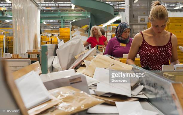 Employees add postmarks to larger items of mail by hand at Deutsche Post AG's sorting facility in Munich Germany on Tuesday Aug 16 2011 Deutsche Post...