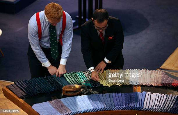 Employees adjust the tie display at the Gieves Hawkes store owned by Trinity Ltd on Saville Row in London UK on Tuesday Aug 7 2012 UK retail sales...