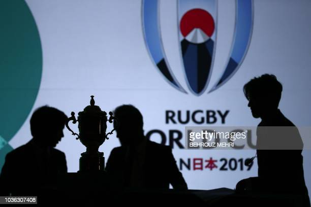 TOPSHOT Employees adjust the Webb Ellis Cup during a kickoff event to mark one year to go to the 2019 Japan Rugby World Cup in Tokyo on September 20...