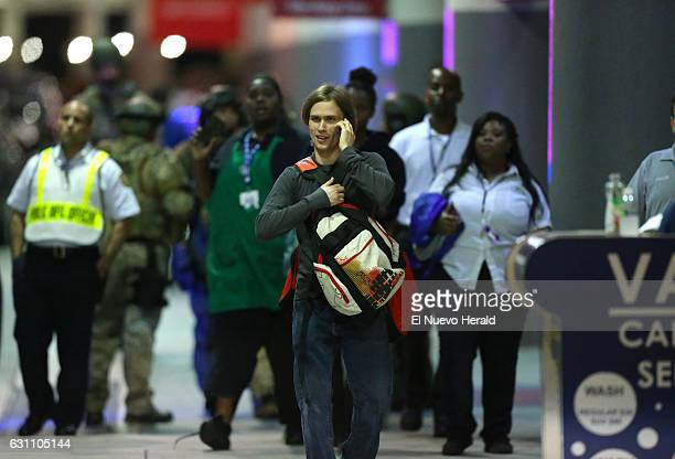 Employees and passengers walking outside terminal 2 after a shooting at Fort LauderdaleHollywood International Airport on Friday Jan 6 in Fort...
