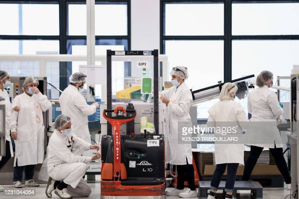 Employees are at work at the factory of British pharmaceutical company GlaxoSmithKline in Wavre on February 8, 2021 where the Covid-19 CureVac...